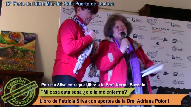 Patricia Silva hace entrega de un ejemplar de reconocimiento a la Prof. Norma Bacchini.