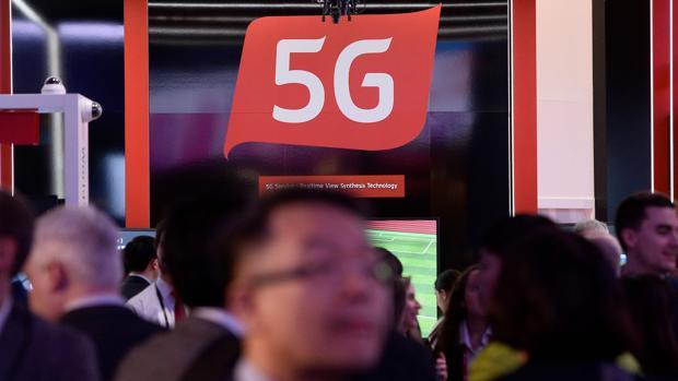 Personas pasan por un stand en donde se informa de las capacidades de las redes 5G - AFP